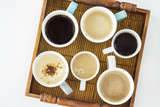 Different cups of coffee on wooden table