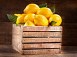 fresh lemons with leaves in a wooden box