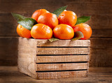 fresh mandarin oranges fruit with leaves in a wooden box - 173399171