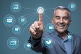 Smiling businessman using a virtual interface - 173430533