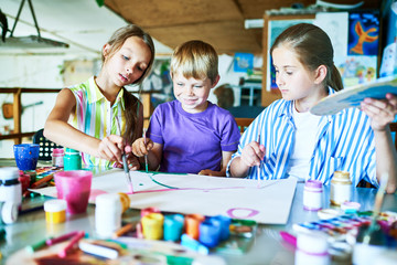 Portrait of three children painting picture together smiling happily while working in art studio during lesson