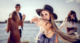 Styled hippie girl dancing at the beach with group of friends - 173433754