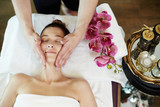 Above view portrait of young woman enjoying face lifting massage lying on table in SPA center and relaxing - 173434158