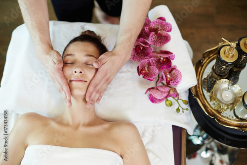 Above view portrait of young woman enjoying face lifting massage lying on table in SPA center and relaxing