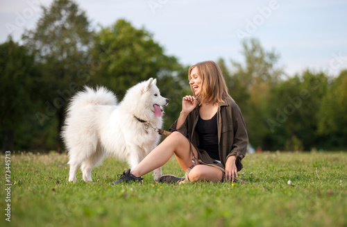 Fototapeta Pretty girl playing with dog on grass at the park