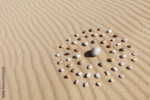 Fotobehang Stenen in het Zand pattern of colored pebbles in the shape of a circle on clean sand