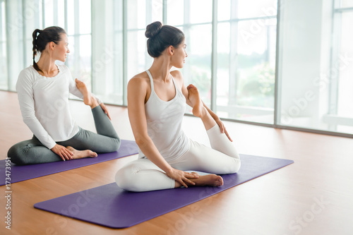 Fototapeta Flexible young woman and her friend making yoga exercise for stretching in gym