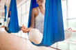 Happy young woman practicing aero yoga in blue hammock