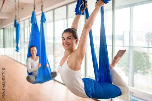 Naklejka Happy female hanging and swinging in hammock during aero yoga workout