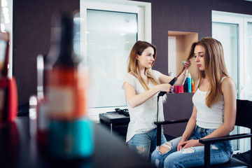 Female hairstylist straightening hair of pretty young blonde customer at hairdressing beauty salon © undrey