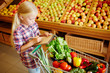 Little consumer making liste of products to buy while shopping in supermarket
