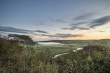Beautiful dawn landscape over English countryside with river slowly flowing through fields - 173499566