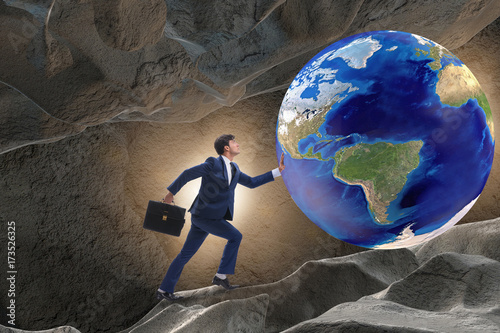 Businessman pushing the world in challenge concept Poster
