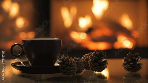 Cap of coffee on table in front of burning fireplace.
