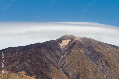Fotobehang Canarische Eilanden View at Mount Teide Volcano peak covered in clouds and lava formations in Teide National Park in Tenerife
