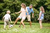 Mutter spielt Fußball mit Familie - 173535308