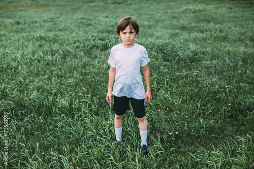 Fotobehang Voetbal Creative portrait of a boy in sportswear outdoors.
