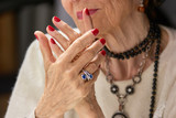 Old womans manicured hands with ring. Old luxury woman beautiful hands with red nails and silver ring. Aged woman keeping hands with red manicure together. - 173566381