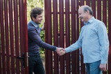 two farmers shaking hands and takling to each other - 173570521