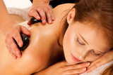 Stone therapy. Woman getting a hot stone massage at spa salon - 173576360