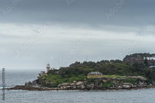 Fotobehang Sydney Sydney, Australia - March 21, 2017: South Head cliffs and park with short Hornby lighthouse, backed by green vegetation under foggy covered sky. Blue-gray sea water up front.