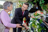 elderly woman buying flowers at funeral service