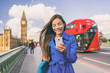 Asian woman using phone walking in London city urban lifestyle. Businesswoman portrait smiling happy holding cellphone in autumn outdoor.
