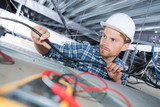 man repairing electrical wiring on the ceiling - 173597575