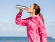 Beautiful girl in sport clothes drinking water after workout on the beach