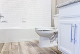 Fototapety Modern white plain clean toilet bathroom, bathtub with shower tiles and hardwood floors with staging in model staging house, home or apartment