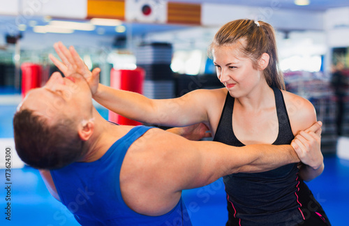 Aluminium Fitness Woman is training with man on the self-defense course in gym.