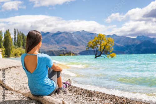 New Zealand travel tourist woman looking at Wanaka lone tree lake landscape Poster