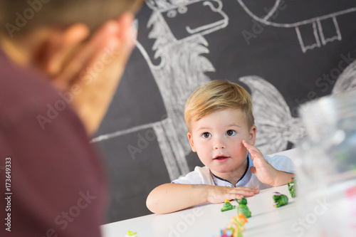 Fototapeta Cute little playfull toddler boy at child therapy session. Private one on one homeschooling with didactic aids.