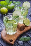 refreshing cold mojito with ice on a black wooden table - 173649563