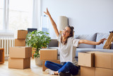 Young woman sitting in new apartment and raising arms in joy after moving in - 173653912