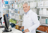 Senior Chemist Using Computer At Counter In Pharmacy - 173655995