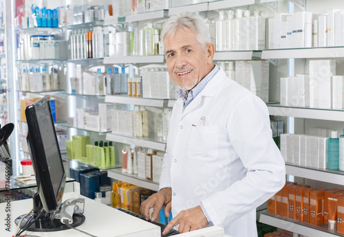 Tuinposter Apotheek Senior Chemist Using Computer At Counter In Pharmacy
