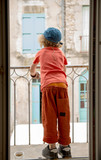 little boy looking out the window, back view - 173657148
