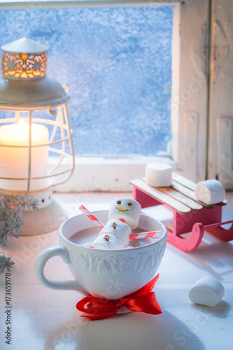 Foto op Canvas Chocolade Relaxing in hot cocoa snowman for Christmas by frozen window
