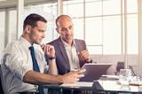 Businessmen working on digital tablet - 173659590