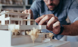 Architect hands making model house - 173667194