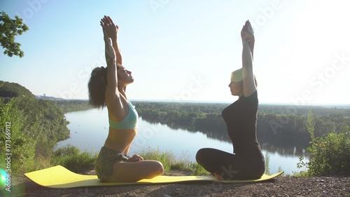 Fototapeta Two girls practice yoga outdoors.