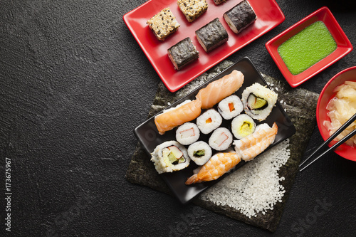 Foto op Canvas Sushi bar Sushi set on red and black dishes and black table background