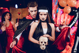 A guy in a vampire costume is standing in charge of a girl dressed as a nun. The girl is holding a skull in her hands - 173678569