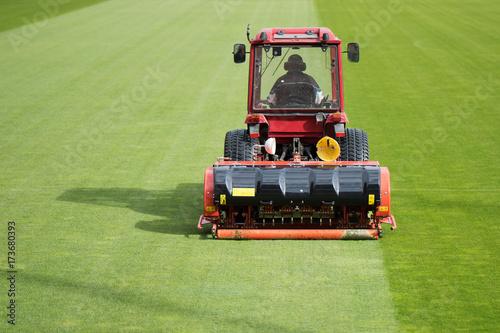 Fotobehang Trekker Man in tractor aerating a soccer field
