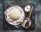 Homemade fresh cheese in  dish and cheesecloth with milk and wooden spoon on rustic background, top view - 173682731
