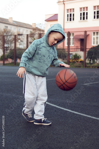 Fotobehang Basketbal little boy kid playing basketball at streetball court