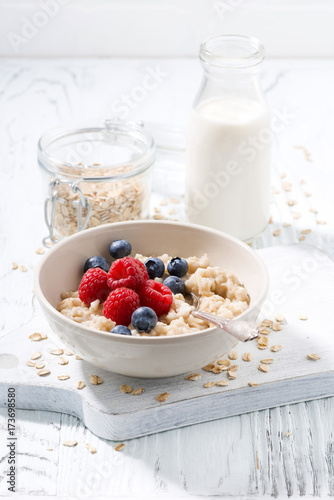 homemade oatmeal with berries and milk on white wooden table, vertical