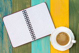 Blank notebook and cappuccino cup