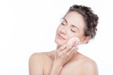 Young woman applying powder to her face. - 173747939